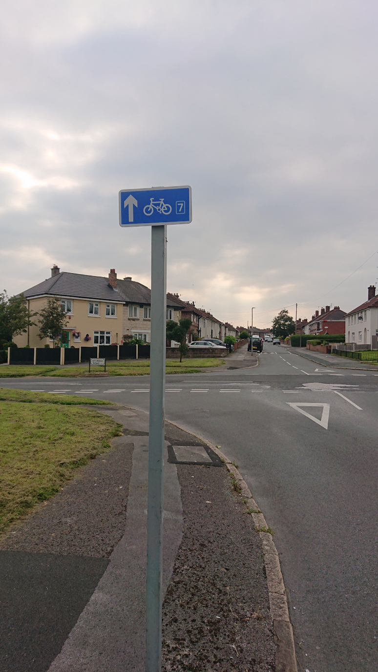 A crossroads on a housing estate, with a small blue cycling sign showing that route 7 is straight on
